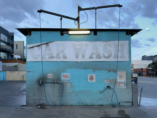 The side of a self-service car wash, a brick structure painted bright teal. The hose attachments hang from a structure on the ceiling. A faded sign, slightly folded over itself, reads \