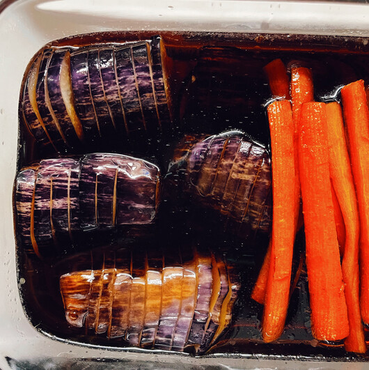 The eggplant and some carrot strips in a dark broth, in a glass container.