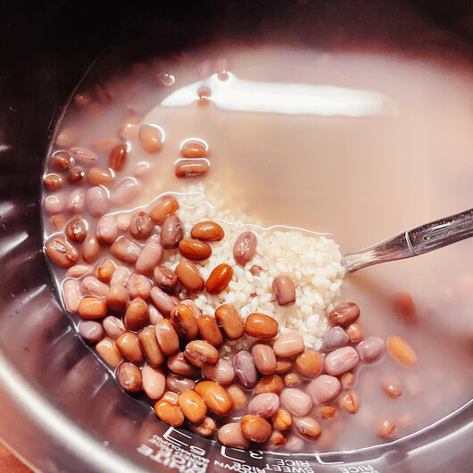 Adzuki beans and rice in a rice cooker bowl, not cooked yet.