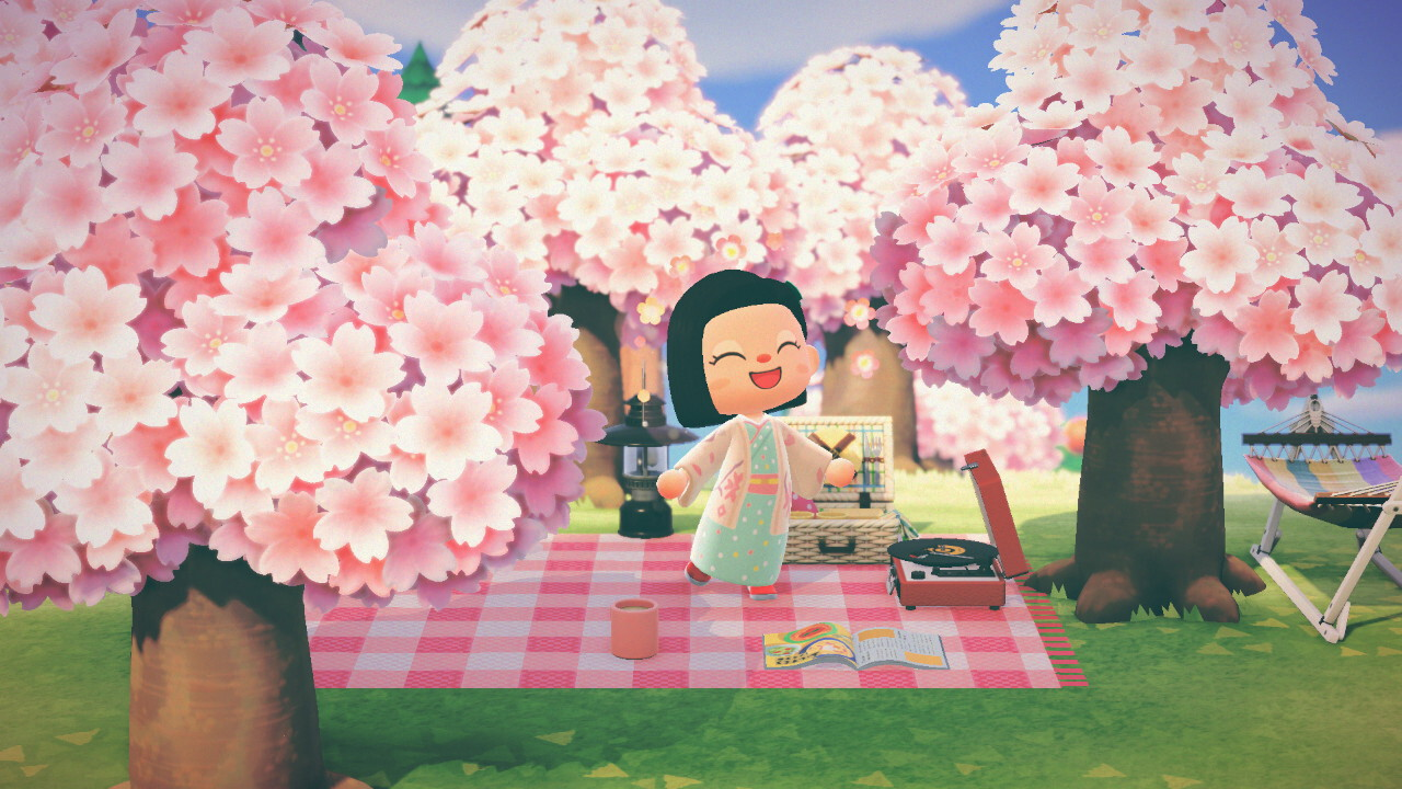 An Animal Crossing: New Horizons screenshot. My villager is wearing a cherry blossom colored yukata and haori coat. A picnic blanket with a lantern, a mug, a magazine, a portable turntable, and a picnic basket is surrounded by trees with blooming cherry blossoms.