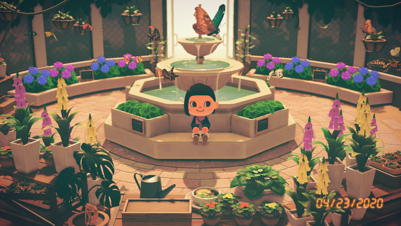 A screenshot from Animal Crossing: New Horizons. My villager sits in front of the fountain in the museum's butterfly room, surrounded by butterflies and flowers.