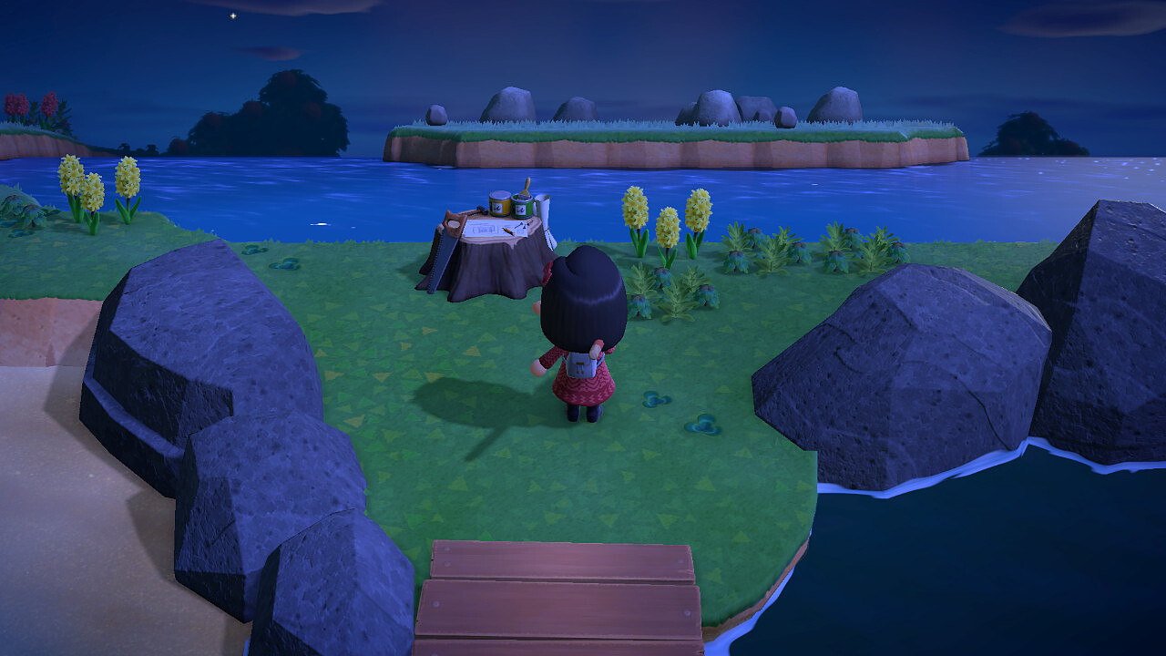 My villager has just arrived at a Nook Miles Mystery Island. A wide lake surrounds a small island with five rocks in the center.