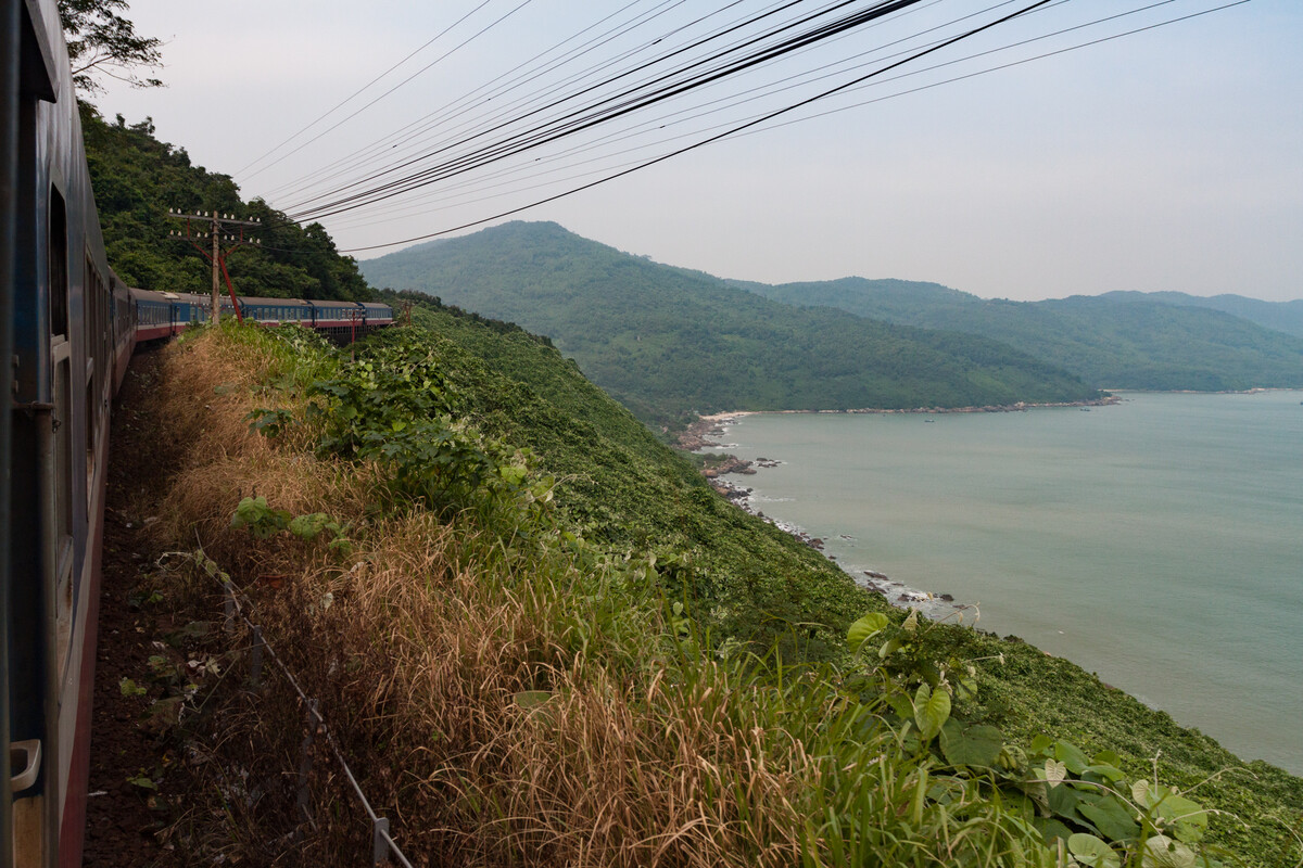 An older train travels along the coast of Vietnam. The tracks are cut into the side of a hill that rolls down to tha rocky coast.