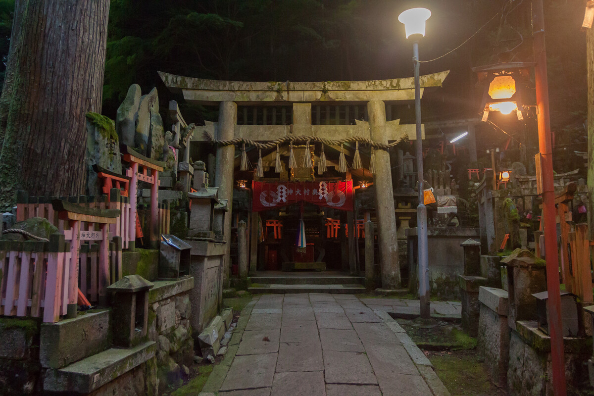 A small shrine at Fushimi Inari Taisha. A small wooden building stands behind an imposing stone torii gate. Dozens of small wooden torii gates are propped on small stone shrines, carved with characters. It is early evening, and the wooded area is illuminated by lights set in lantern enclosures.